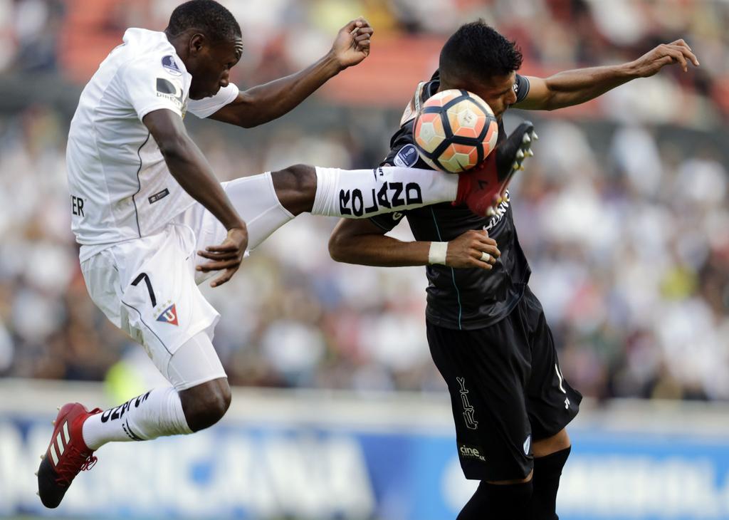 In this Wednesday, Aug. 2, 2017 photo, Anibal Chala of Ecuador's Liga Deportiva Universitaria, left, fights for the ball with Pablo Pedraza of Bolivia...