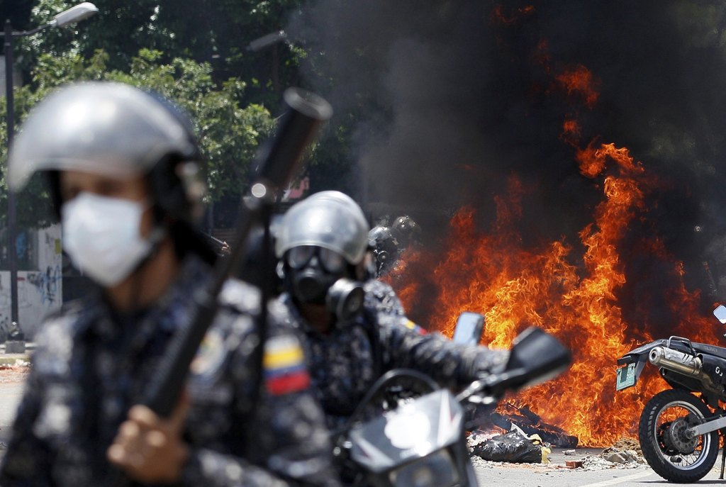 In this Sunday, July 30, 2017 photo, Bolivarian National Guards move away from the flames after an explosion in Altamira Plaza during clashes with ant...
