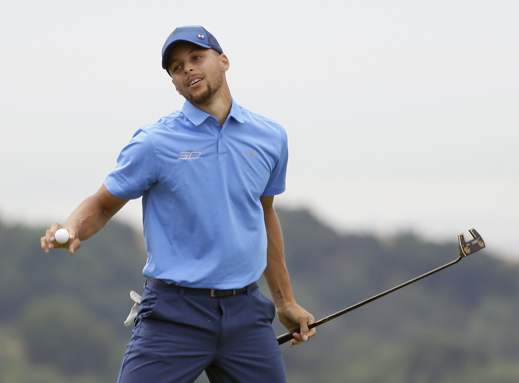 Golden State Warriors NBA basketball player Stephen Curry reacts after making a putt to save par on the 18th green during the Web.com Tour's Ellie Mae...