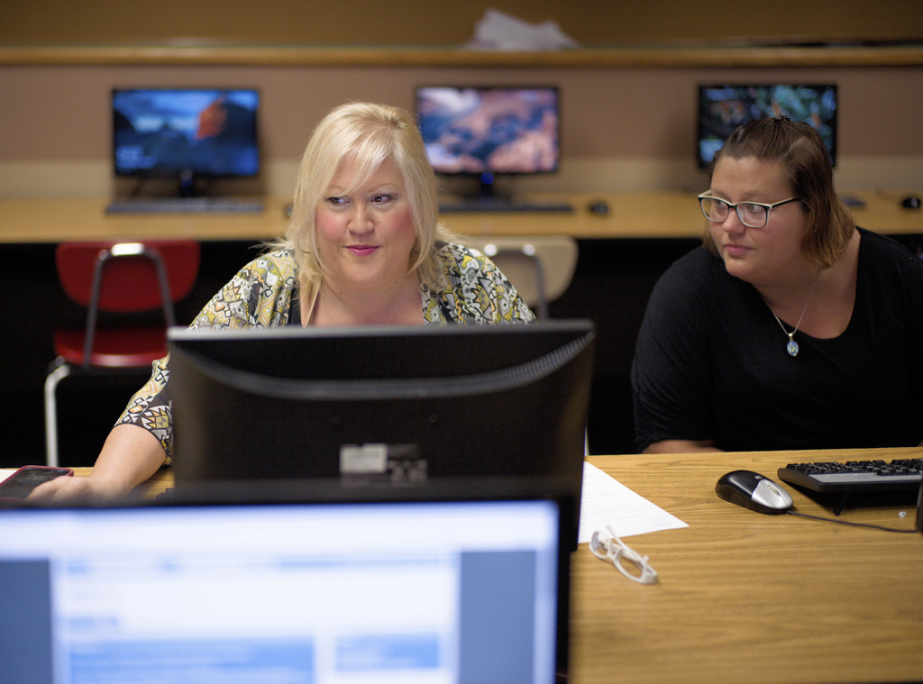 In this Thursday, July 27, 2017, photo, Cheryl Bast, left, is accompanied by her daughter Liz Pierson, as she works on an application for a position w...