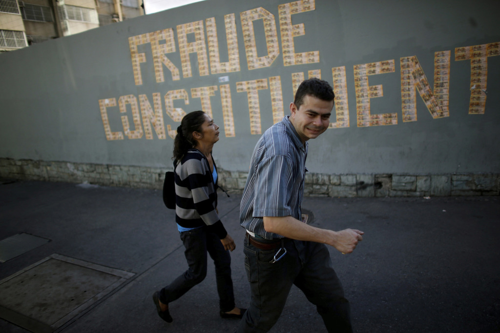 """FILE - In this July 30, 2017 file photo, pedestrians walk past a graffiti that reads in Spanish """"Constituent Assembly Fraud,"""" in Caracas, Venezuela. W..."""