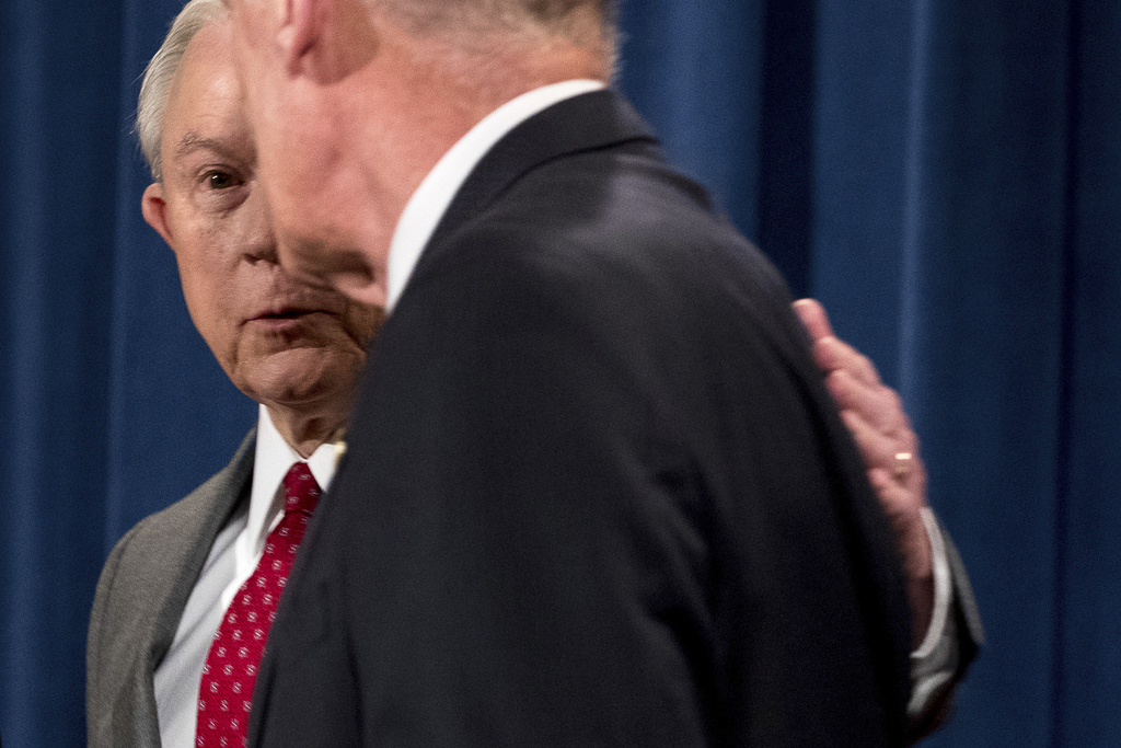 Attorney General Jeff Sessions, left, speaks with Director of National Intelligence Dan Coats as they depart a news conference at the Justice Departme...