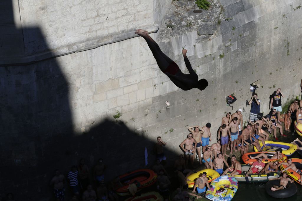 Spectators watch as a diver jumps from the Old Mostar Bridge during 451th traditional annual high diving competition, in Mostar, Bosnia, 140 kilometer...