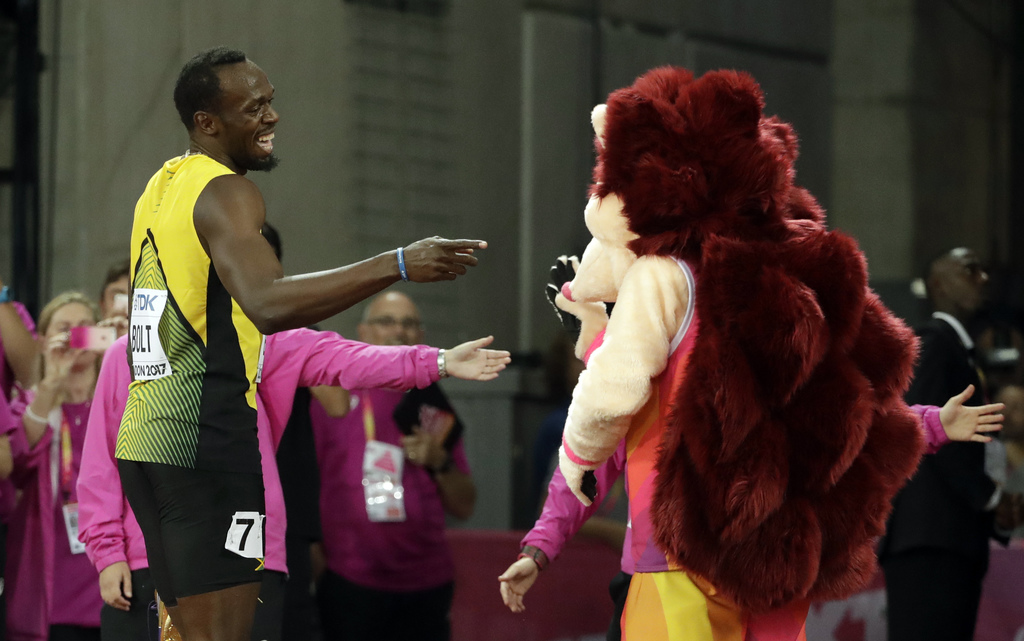 Jamaica's Usain Bolt jokes with mascot Hero the Hedgehog after his men's 100m heat during the World Athletics Championships in London Friday, Aug. 4, ...
