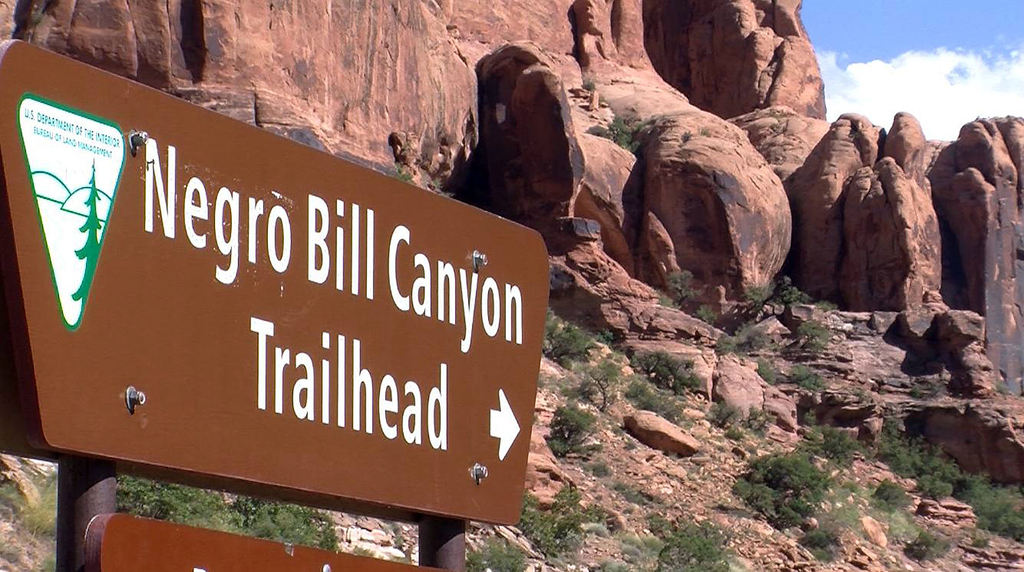 FILE - This undated file photo shows a sign at the entrance of the Negro Bill Canyon Trailhead in Moab, Utah. A Utah state commission is recommending ...