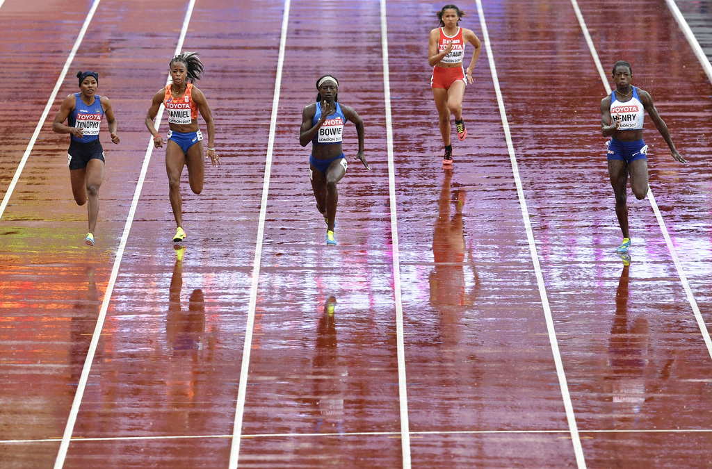 United States' Tori Bowie, center, runs through the rain in a Women's 100m first round heat during the World Athletics Championships in London Saturda...