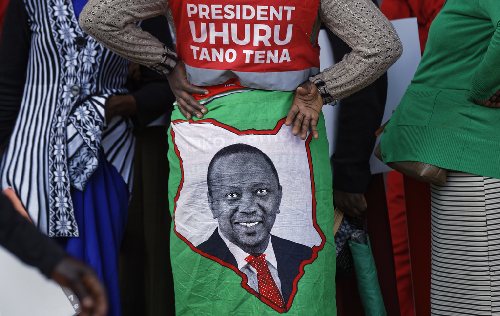 """A supporter wears a cloth wrap showing Kenya's President Uhuru Kenyatta, with writing in Swahili reading """"President Uhuru, Five More"""" referring to the..."""
