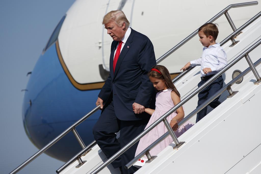 President Donald Trump walks down the steps of Air Force One with his grandchildren, Arabella Kushner, center, and Joseph Kushner, right, after arrivi...