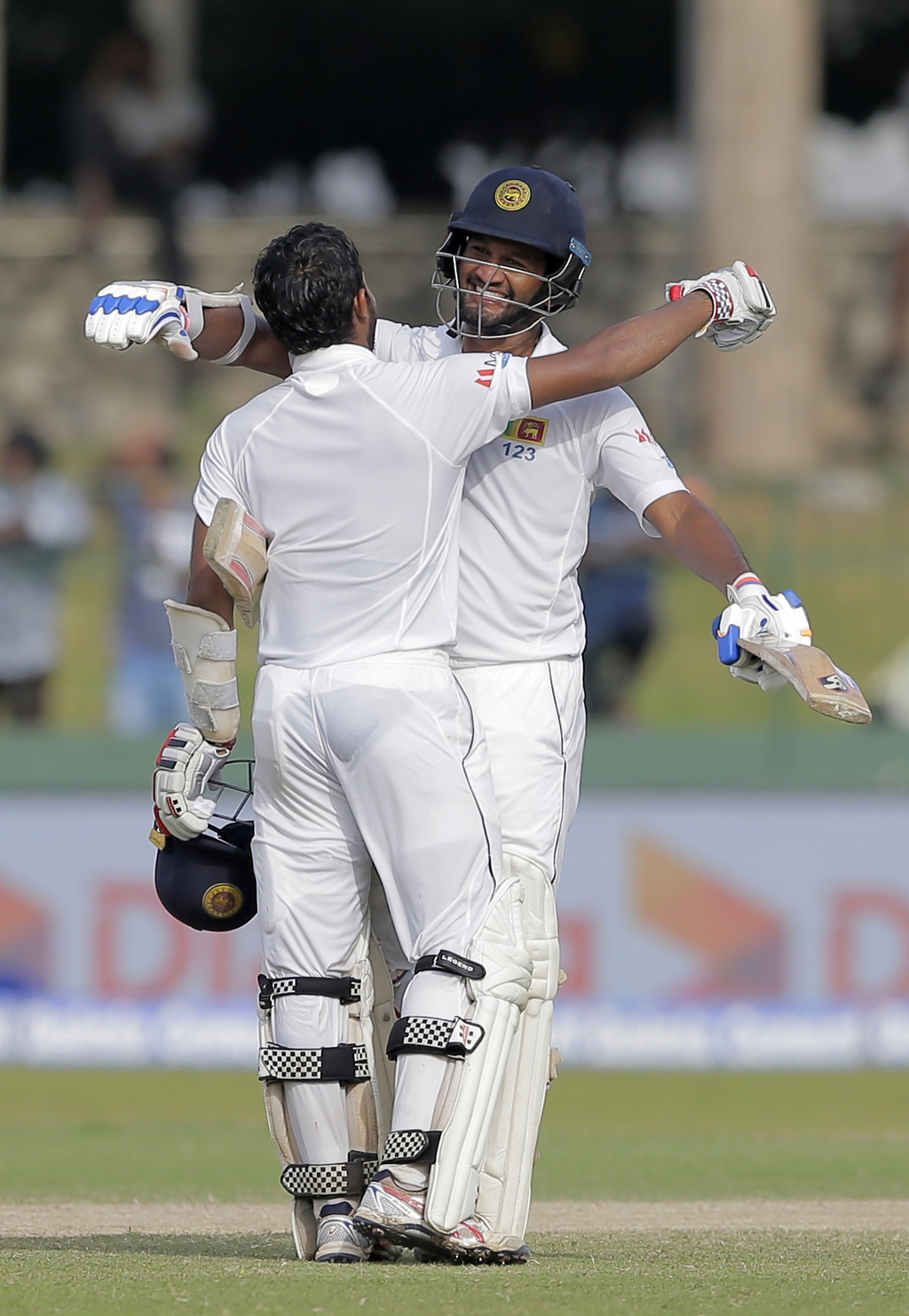 Sri Lanka's Dimuth Karunaratne, right, hugs to congratulate teammate Kusal Mendis on scoring a century during their second cricket test match against ...