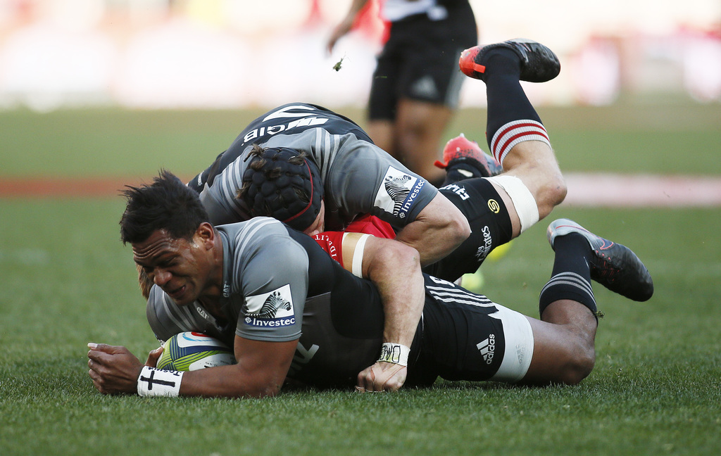 Crusaders Seta Tamaniva, left, is tackled during the Super Rugby final between South Africa's Lions and New Zealand's Crusaders, at Ellis Park stadium...