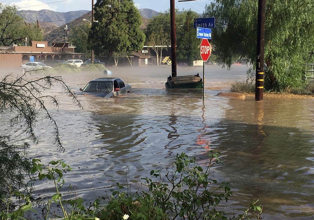 In this Thursday, Aug. 3, 2017 photo provided by @brandibrands shows a car submerged by water after a flash flood in Acton, Calif. The Southern Califo...