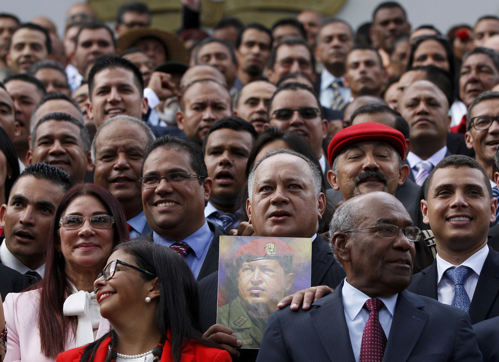 In this  Friday, Aug. 4, 2017 photo, Venezuela's Constitutional Assembly member Diosdado Cabello holds an image of Venezuela's late President Hugo Cha...