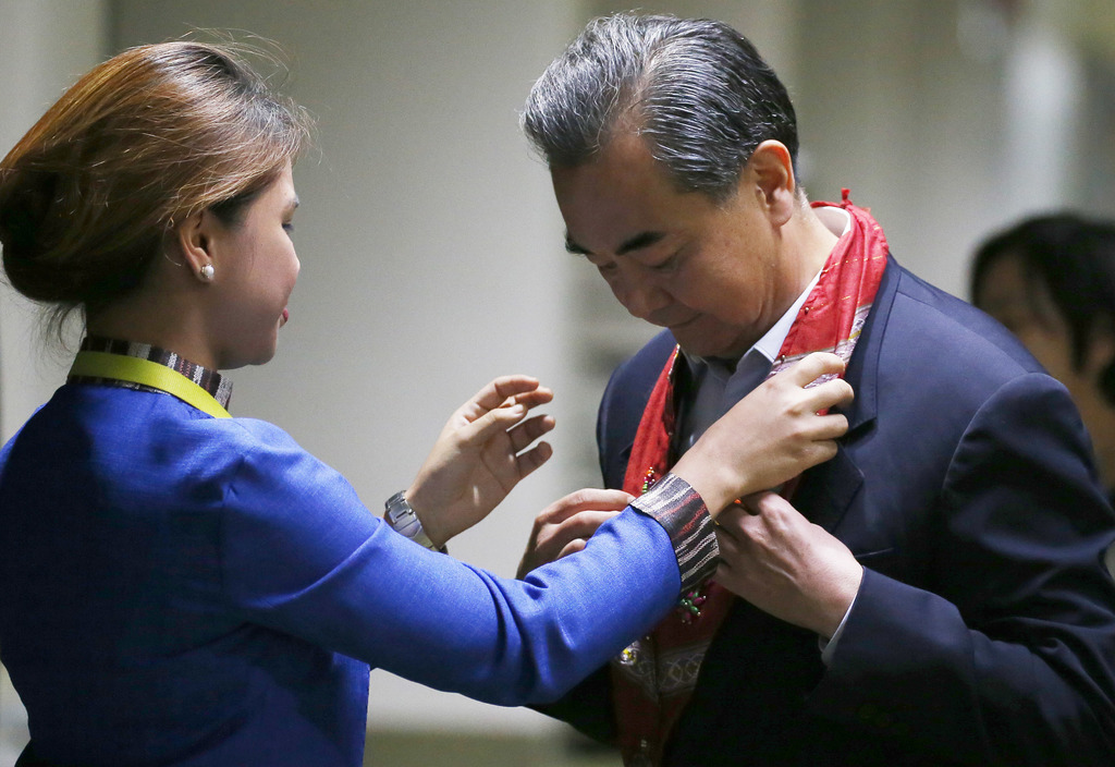 Chinese Foreign Minister Wang Yi receives a lei upon arrival to take part in the 50th ASEAN Foreign Ministers' Meeting and its Dialogue Partners, Satu...