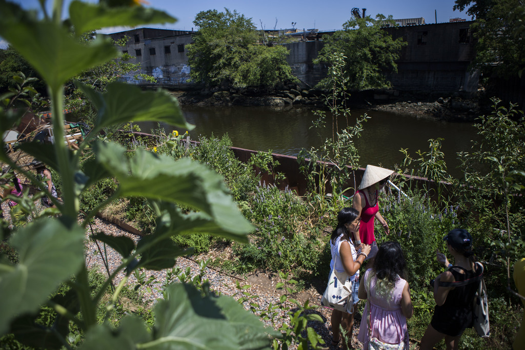 In this Aug. 1, 2017, photo, Amanda McDonald Crowley, center, leads a group of Kickstarter interns the through the Swale garden in New York. The Swale...
