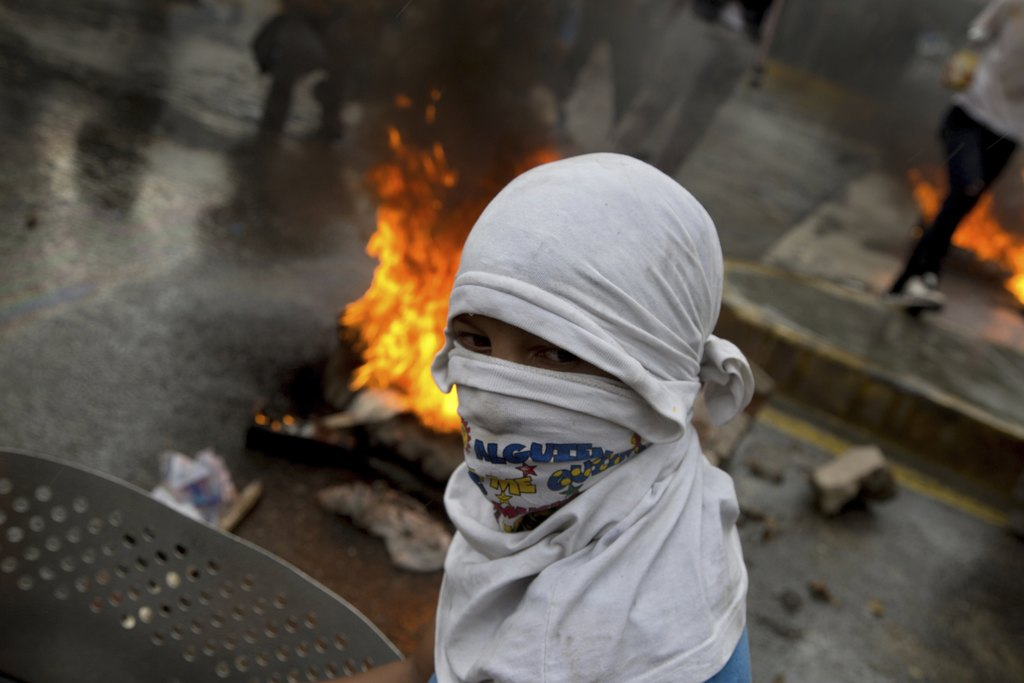 A masked anti-government demonstrator walks past next to a burning barricade during a protest against the installation of a constitutional assembly in...