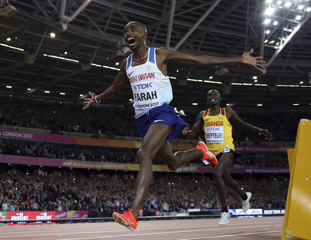 Britain's Mo Farah celebrates after winning the gold medal in the men's 10,000-meter final during the World Athletics Championships in London Friday, ...