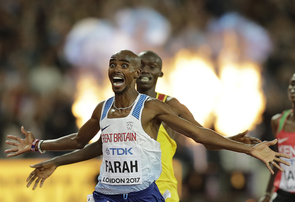 Britain's Mo Farah, left, celebrates after winning the Men's 10,000 meters final during the World Athletics Championships in London Friday, Aug. 4, 20...