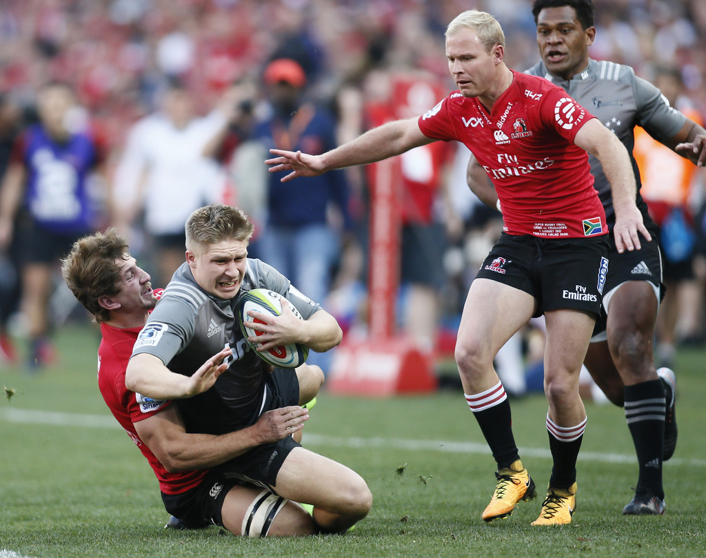 Crusaders Jack Goodhue is tackled by Crusaders Kwagga Smith during the Super Rugby final between South Africa's Lions and New Zealand's Crusaders, at ...