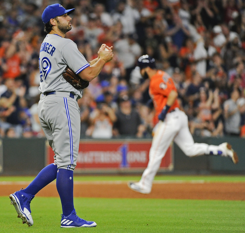 Toronto Blue Jays relief pitcher Mike Bolsinger, left, walks off the mound as Houston Astros' Marwin Gonzalez, right, rounds the bases after hitting a...