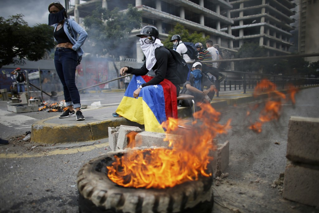 Masked anti-government demonstrators stend to a burning barricade during a protest against the installation of a constitutional assembly in Caracas, V...