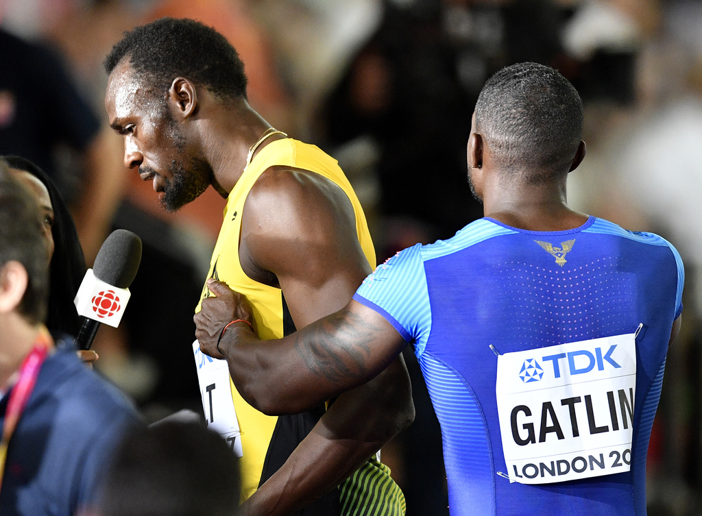 United States' Justin Gatlin, right, jokes with Jamaica's Usain Bolt in the mixed zone following their heats in the Men's 100 meters during the World ...