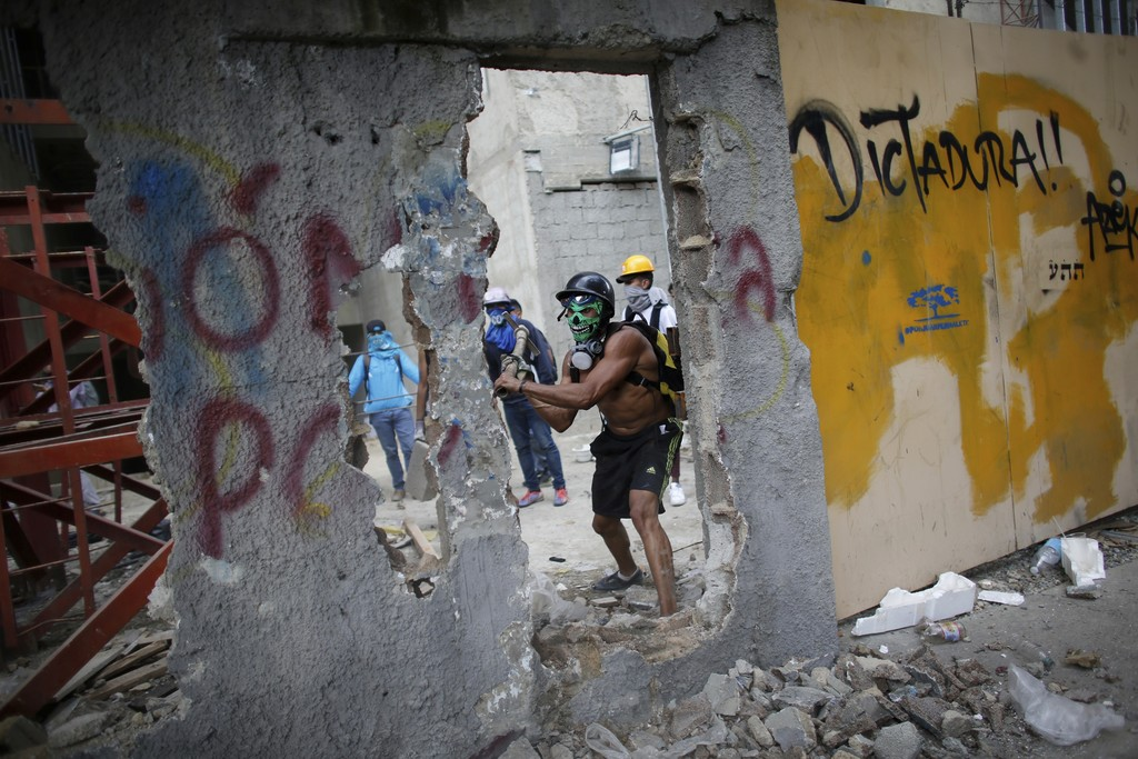 In this Friday, Aug. 4, 2017 photo, a masked anti-government demonstrator breaks down a wall to release pieces of concrete to throw at Bolivarian Nati...