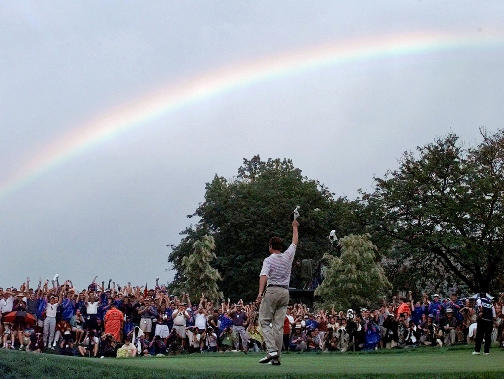 FILE - In this Aug. 17, 1997, file photo, a rainbow soars above Davis Love III, of Sea Island, Ga., after he won the PGA Championship at Winged Foot G...