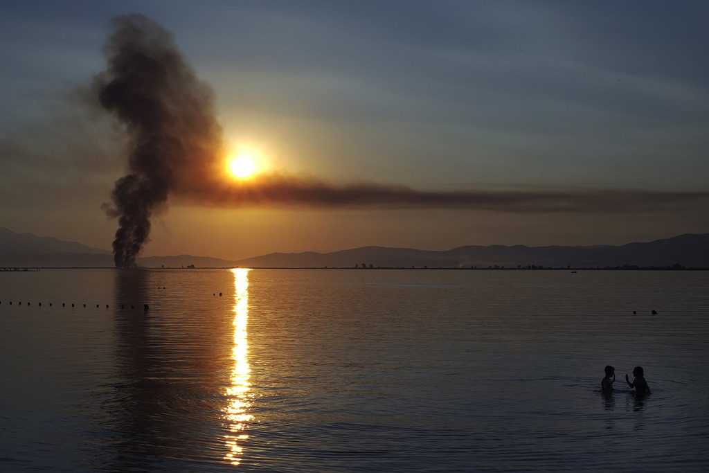 Children play in the sea as smoke from a fire rises in the background during a sunset at Keramoti, northern Greece, on Sunday, July 30, 2017. August i...