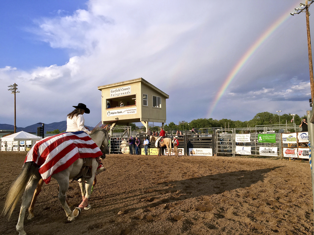 A flag-draped riderless horse to honor the fallen is led through the arena at the Garfield County Fair and Rodeo in Rifle, Colo., as a rainbow arcs in...