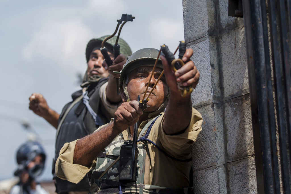 Indian paramilitary soldiers use slingshots to shoot glass marbles at Kashmiri protesters in Srinagar, Indian controlled Kashmir, Friday, Aug. 4, 2017...