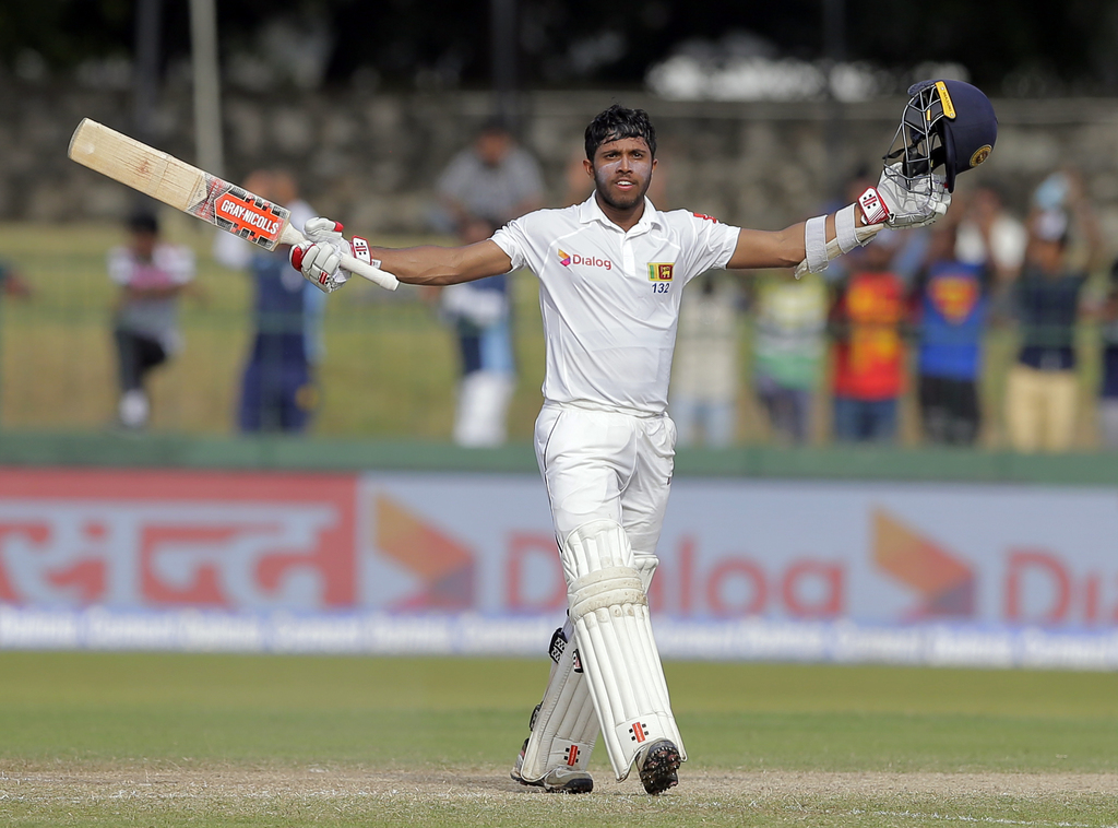 Sri Lanka's Kusal Mendis raises his bat and helmet to celebrate scoring a century during their second cricket test match against India in Colombo, Sri...