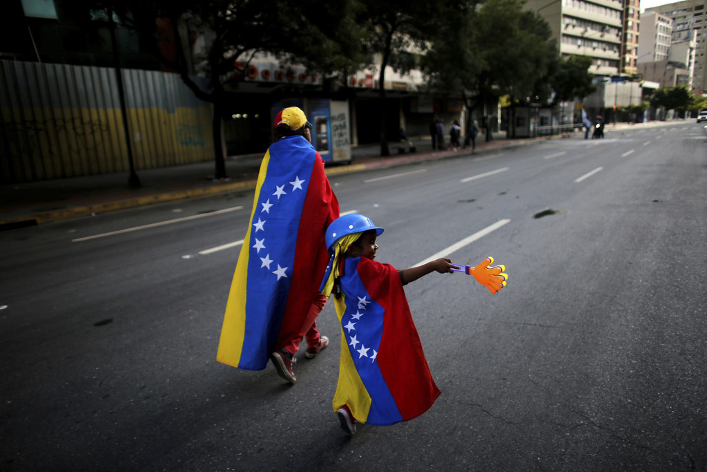 FILE- In this July 30, 2017 file photo, an anti-government demonstrator and her daughter wrapped in the Venezuelan flag walk on an empty street in Car...