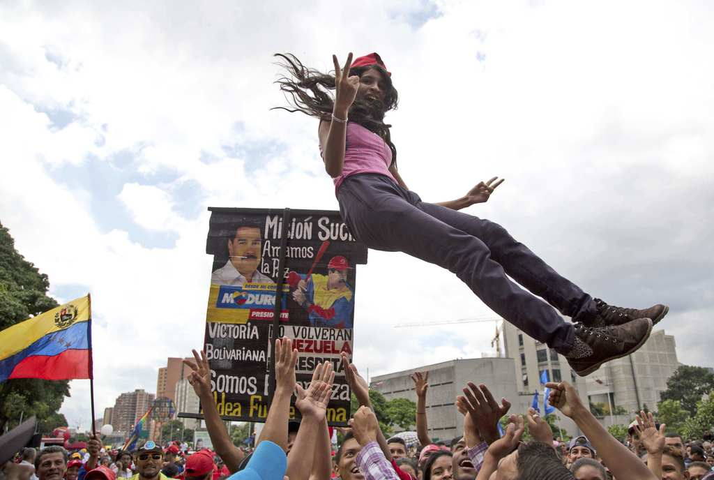 In this Friday, Aug. 4, 2017 photo, a young supporter of Venezuela's President Nicolas Maduro is tossed into the air before the start of a march to th...