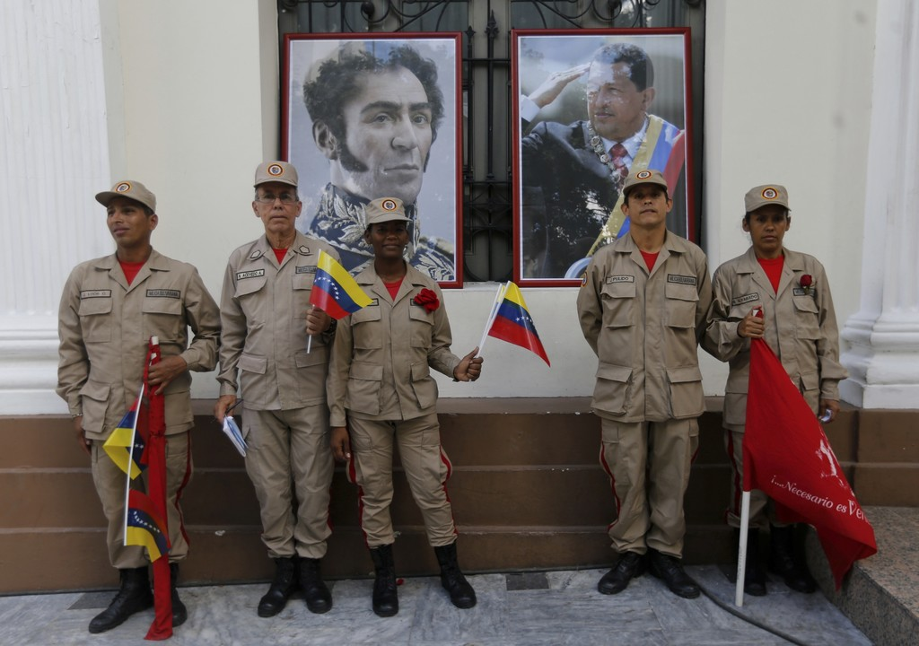 In this Friday, Aug. 4, 2017 photo, militia members pose for a photo next to images of Venezuelan independence hero Simon Bolivar, left, and late Pres...