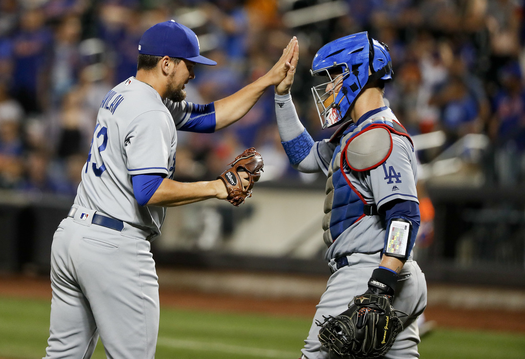Los Angeles Dodgers relief pitcher Luis Avilan (43) celebrates with catcher Yasmani Grandal after recording a save against the New York Mets in a base...