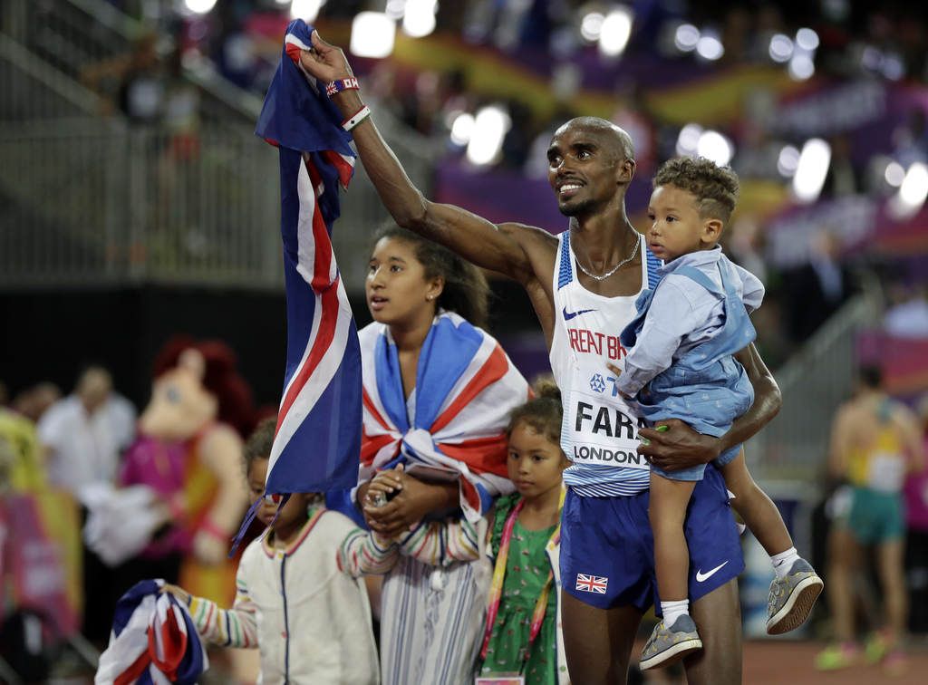 Britain's Mo Farah holds his son Hussein Mo as he celebrates after winning the gold medal in the men's 10,000-meter final during the World Athletics C...