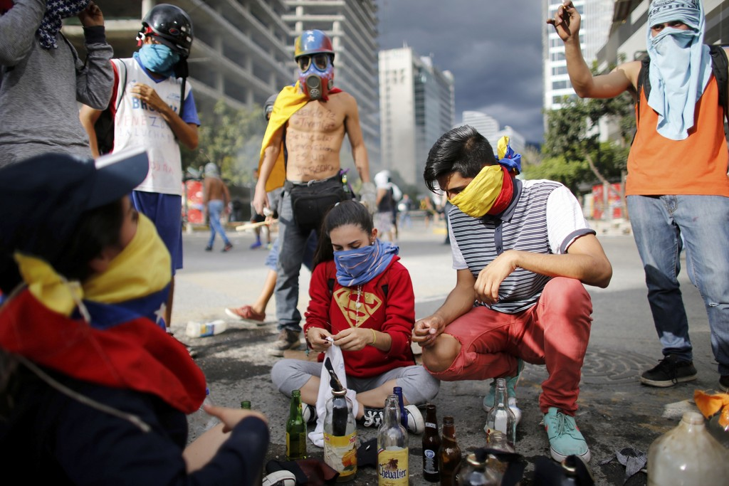 Anti-government demonstrators prepare homemade petrol bombs that will be used against Venezuelan Bolivarian National Police, during a protest against ...
