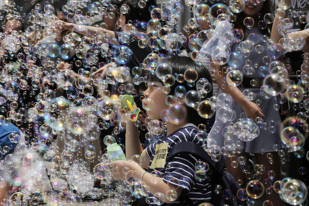 """A boy plays with bubbles during an art display titled """"Bubble Up"""" created by Japanese artist Shinji Ohmaki in Hong Kong, Wednesday, Aug. 2, 2017. (AP ..."""
