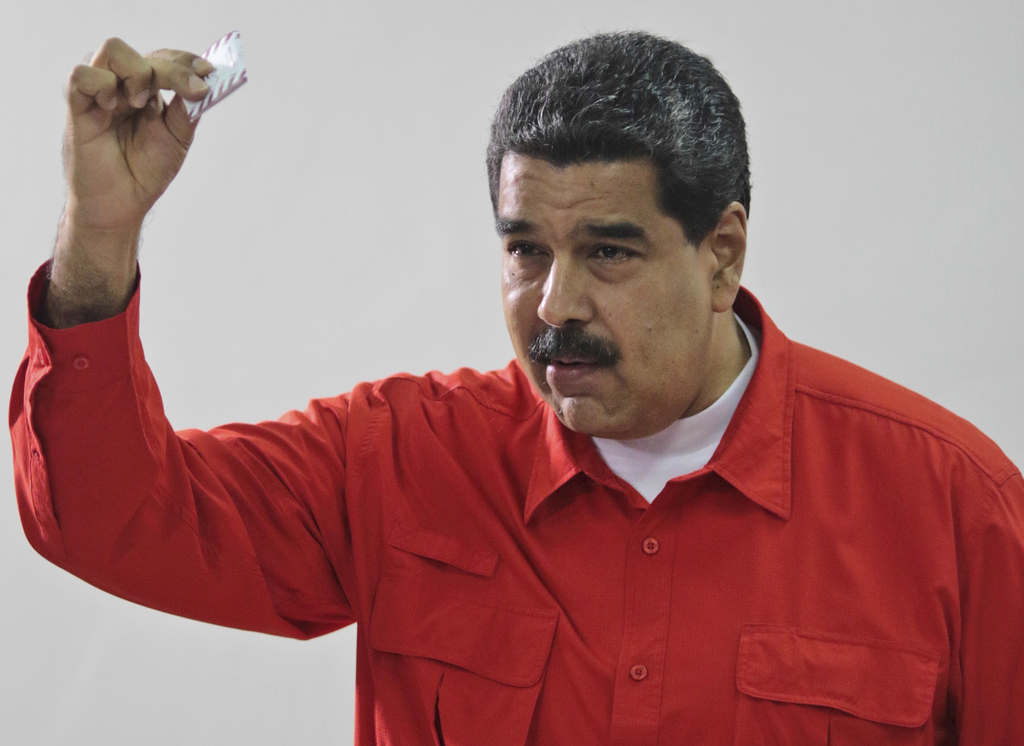 FILE - In this July 30, 2017 file photo, released by the Miraflores Press Office, Venezuela's President Nicolas Maduro shows his ballot after casting ...