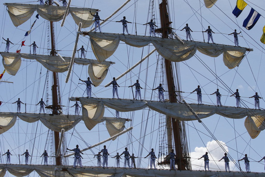 Mexican Navy crew members stand on the sails of the ARM Cuauhtemoc tall ship as it prepares to dock in the South Harbor in Manila, Philippines, for a ...