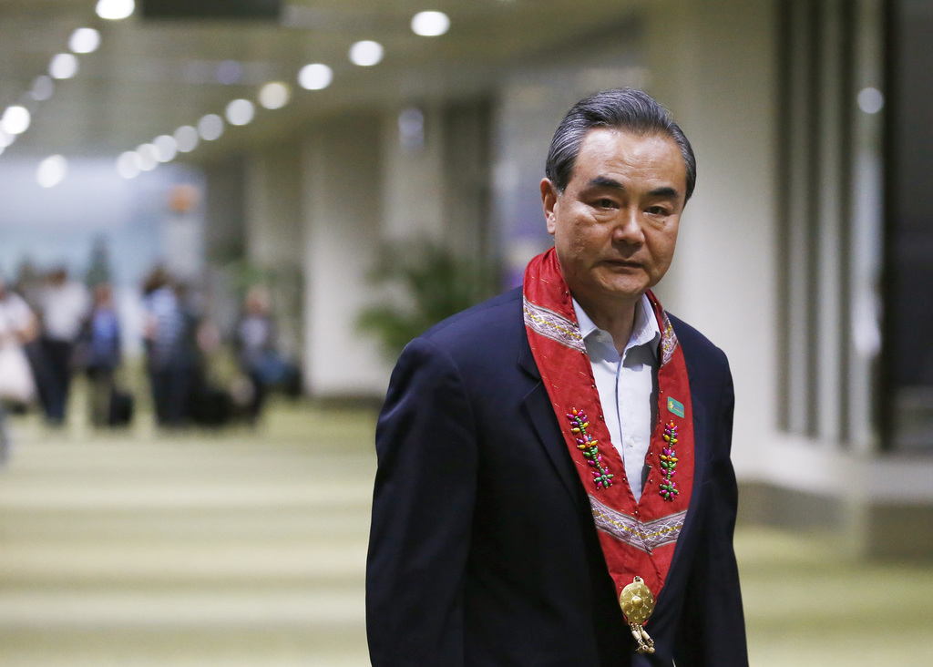 Chinese Foreign Minister Wang Yi after receiving a lei (sash) greeting, upon arrival to take part in the 50th ASEAN Foreign Ministers' Meeting and its...