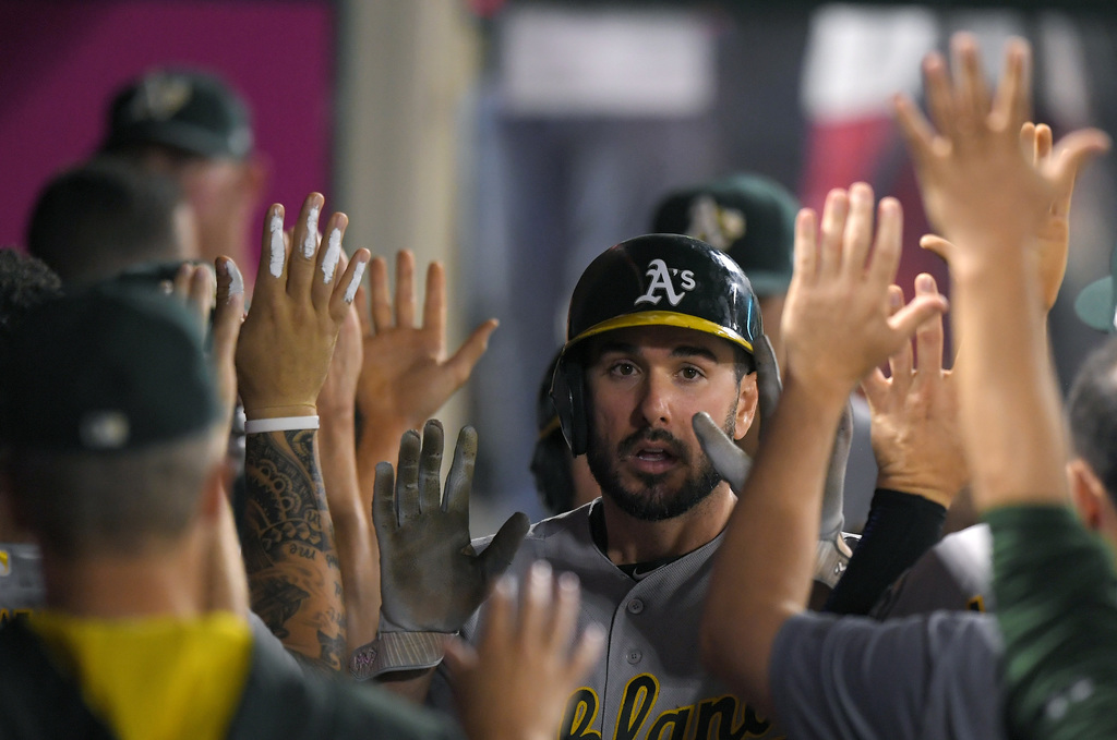Oakland Athletics' Matt Joyce, center, is congratulated by teammates after scoring on a double by Khris Davis during the fifth inning of the team's ba...