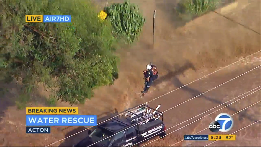 This Thursday, Aug. 3, 2017 aerial image made from video provided by KABC-7 shows a motorist being airlifted from his truck after a flash flood hit in...