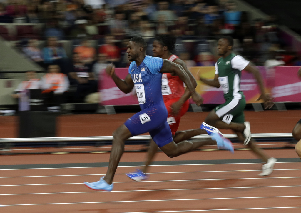 United States' Justin Gatlin, left, competes in a men's 100m heat during the World Athletics Championships in London Friday, Aug. 4, 2017. (AP Photo/M...