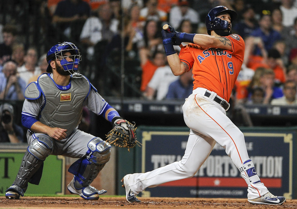Houston Astros' Marwin Gonzalez follows through on a three-run home run off against the Toronto Blue Jays as catcher Russell Martin watches during the...