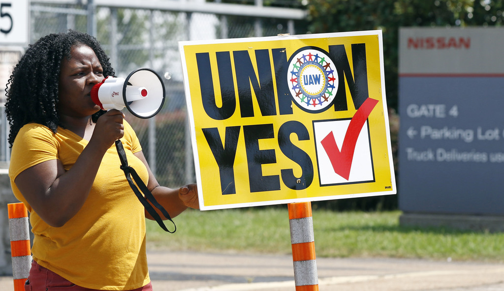 A UAW supporter uses a bull horn to remind eligible workers to vote for the union while standing outside an employee vehicle entrance at the Nissan ve...