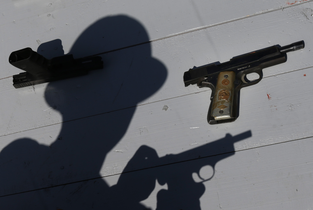 A Mexican Army soldier shows a set of hand guns sporting a gold plated grips, part of a lot of weapons slated for destruction in Mexico City, Tuesday,...