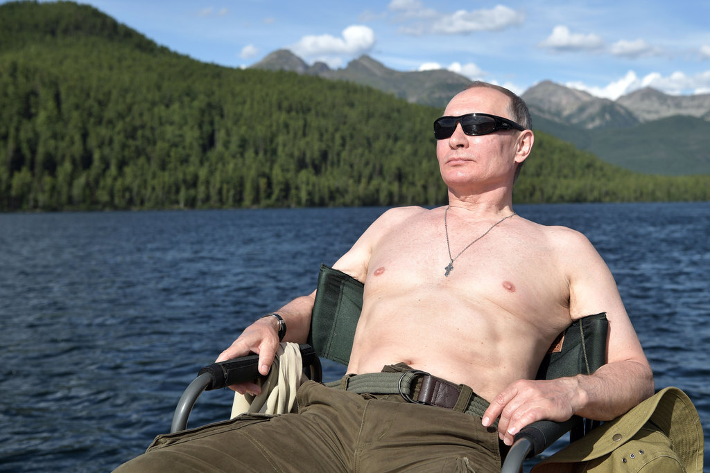 In this photo released by Kremlin press service on Saturday, Aug. 5, 2017, Russian President Vladimir Putin rests after fishing during a mini-break in...