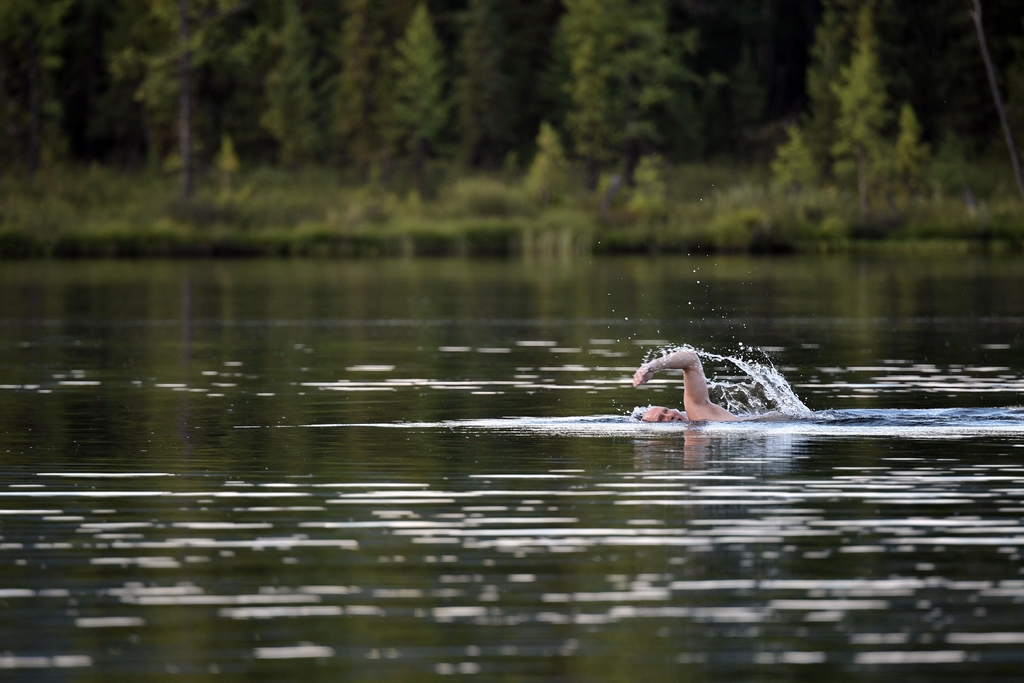 In this photo released by Kremlin press service on Saturday, Aug. 5, 2017, Russian President Vladimir Putin swims during a mini-break in the Siberian ...