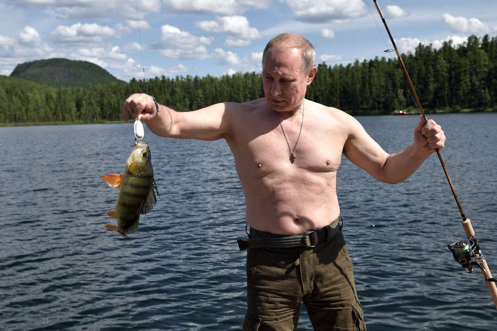 In this photo released by Kremlin press service on Saturday, Aug. 5, 2017, Russian President Vladimir Putin holds a fish he caught while fishing durin...